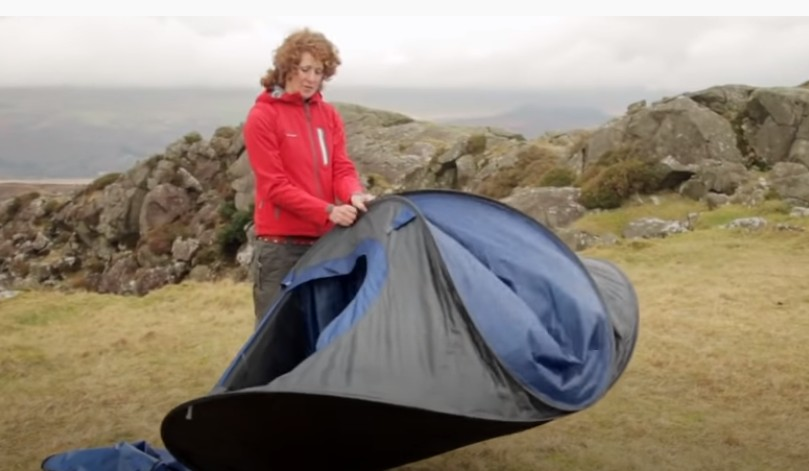 Woman Folds the top two poles together